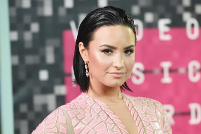 Demi Lovato, with short brown hair tucked behind ears, is wearing a pink dress