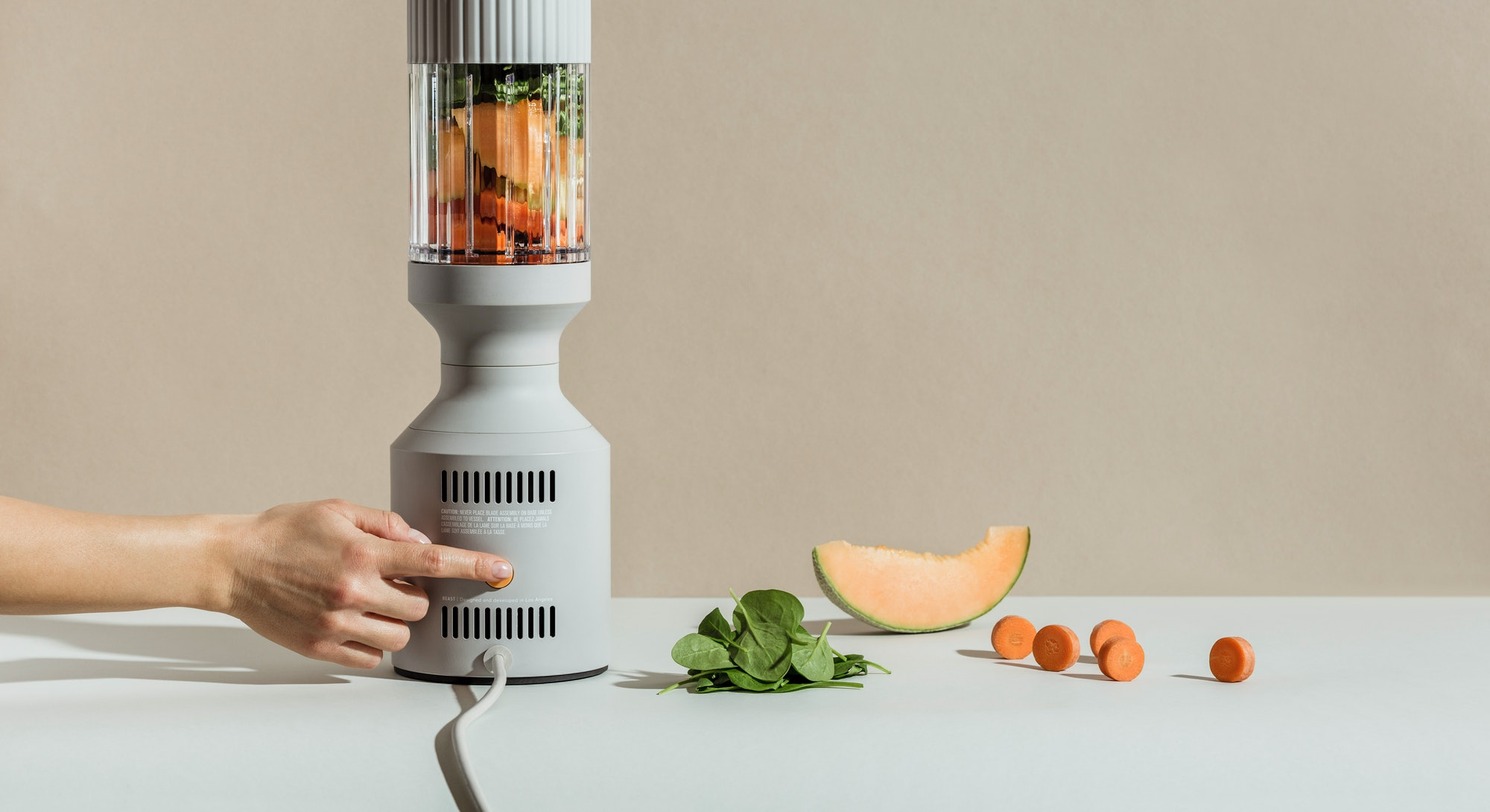 A B10 blender is seen with papaya, greens, and other fruits inside the blending glass.