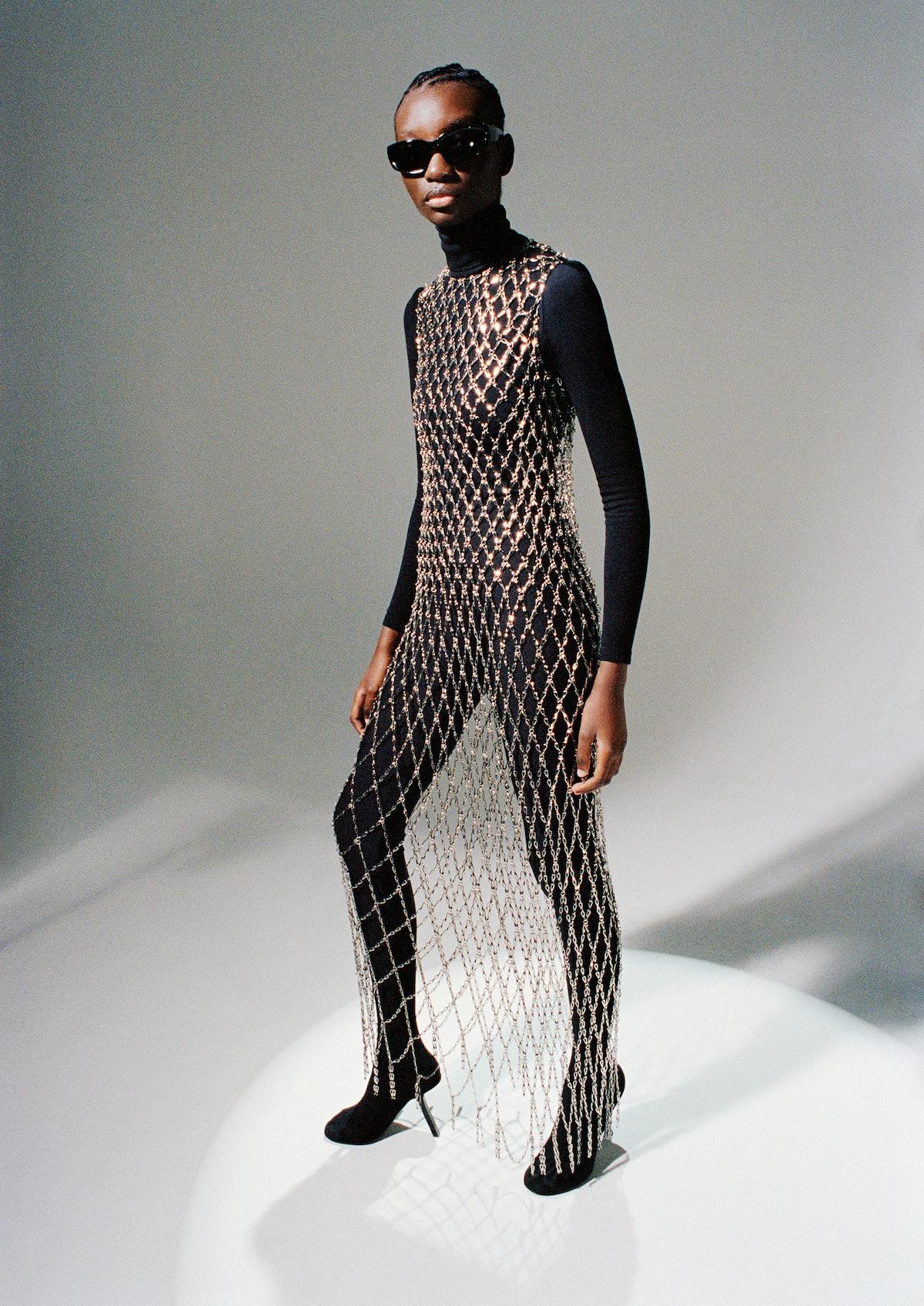 Assa Baradji wears a Balenciaga chain dress, sunglasses, and pantalegging shoes; Wolford turtleneck bodysuit.