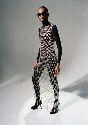 Assa Baradji wears a Balenciaga chain dress, sunglasses, and pantalegging shoes; Wolford turtleneck ...