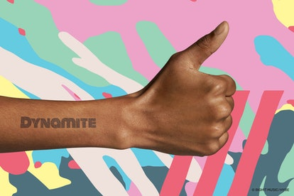 An arm making a thumbs up shows the word Dynamite on it, which was created using the Inkbox BTS temporary tattoo collection