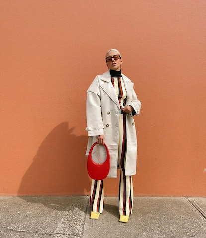 Woman wearing striped co-ord set with trench coat and red bag.