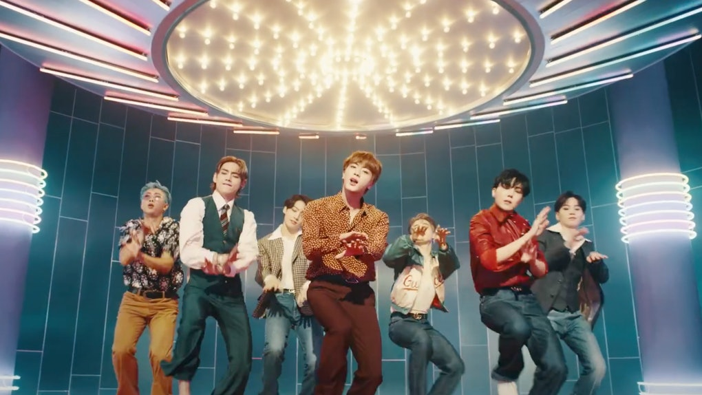 "The members of BTS dance in the music video for ""Dynamite."""