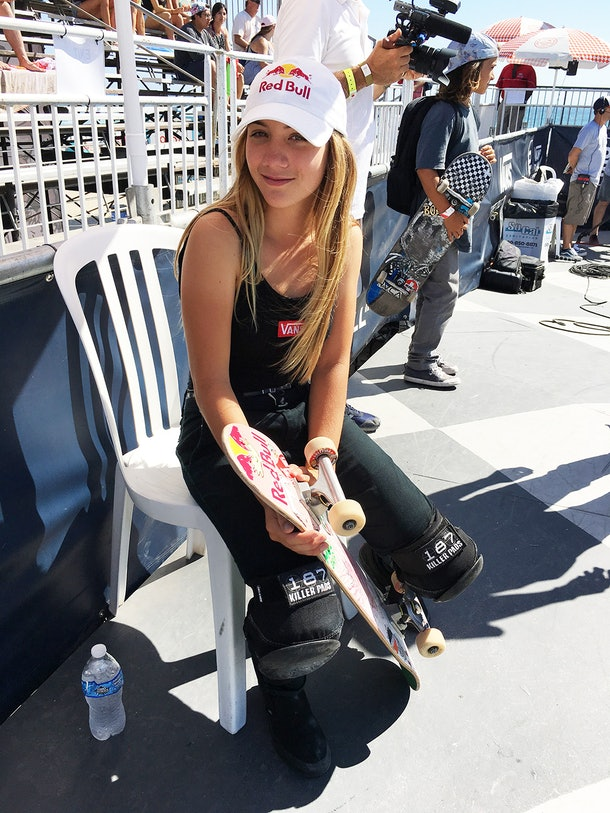 Brighton Zeuner sits in a plastic chair in the shade in front of a set of bleachers, holding a skateboard and wearing a Red Bull baseball cap. She faces the camera at a angle and smiles slightly