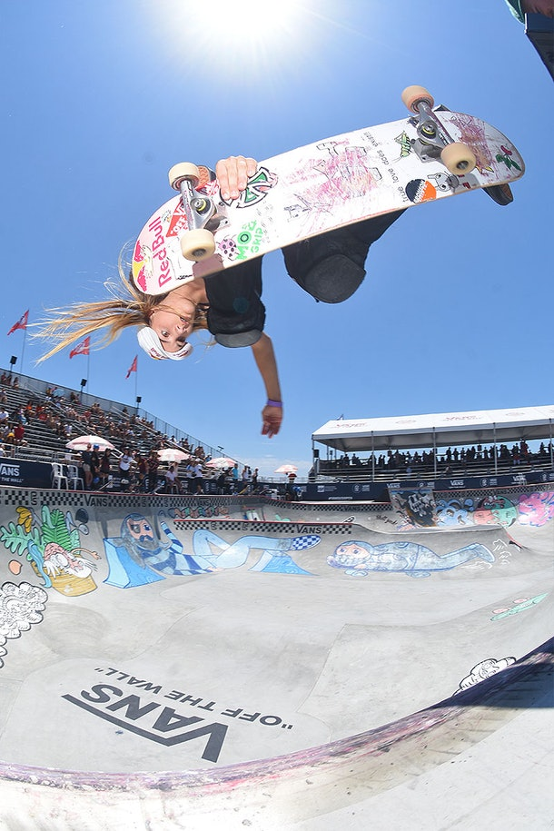 Teen skateboard champion Brighton Zeuner, seen in mid-air and upside down, as she performs a flip at the top of a ramp
