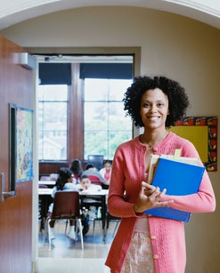 teacher standing outside of her classroom, holding a stack of folders