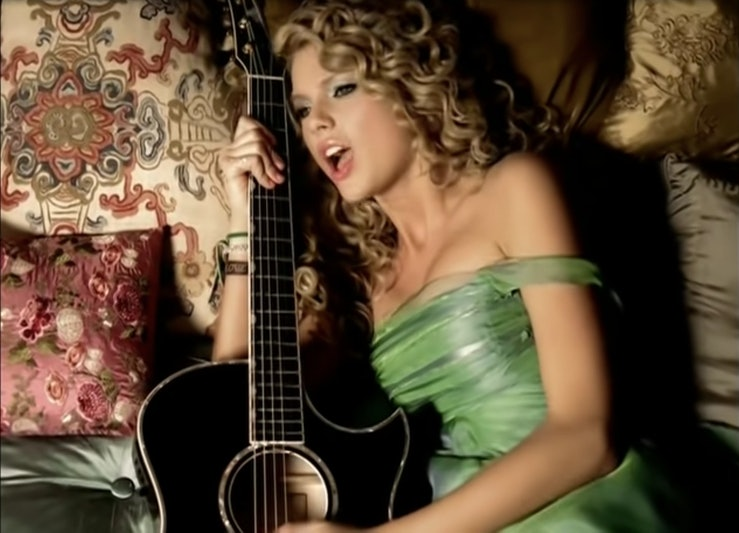 """A still from """"Teardrops On My Guitar."""" It shows Taylor Swift laying in a light green gown clutching her guitar."""