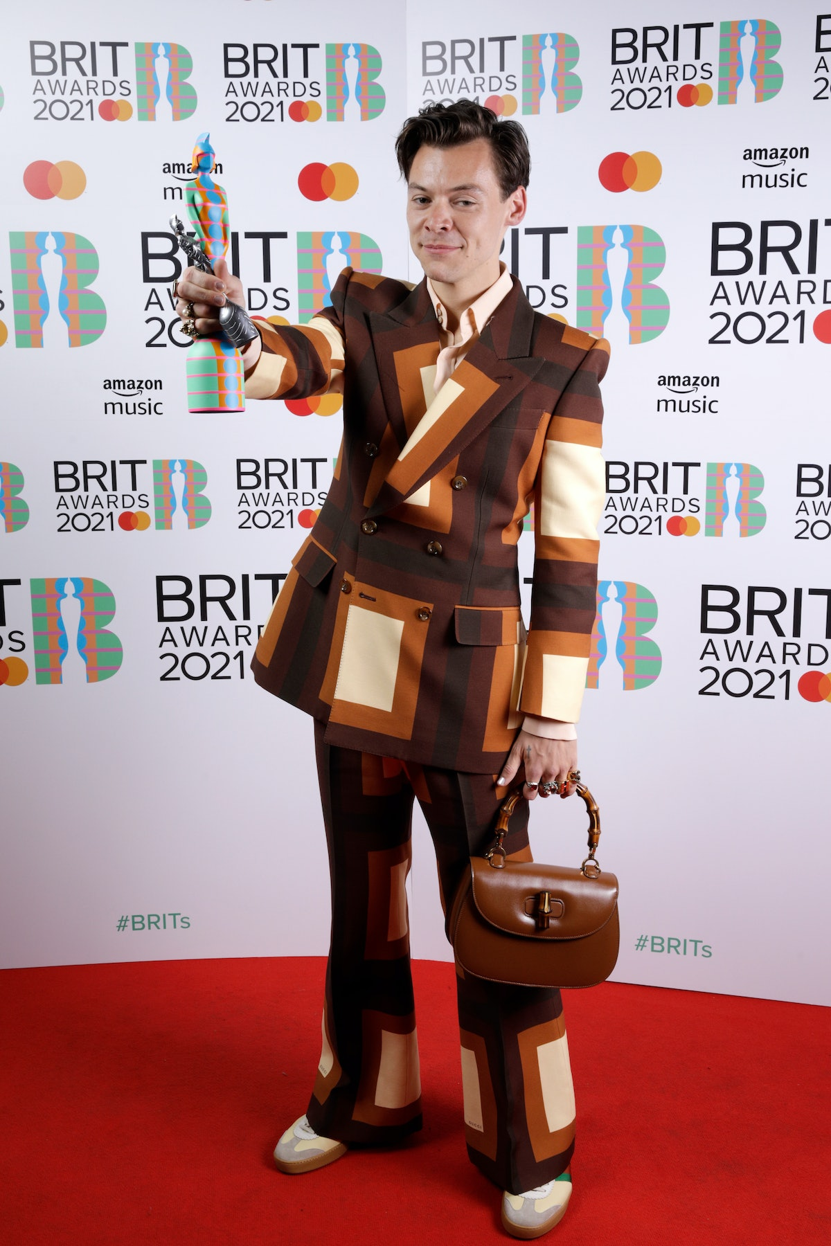 harry styles carrying his BRIT Award