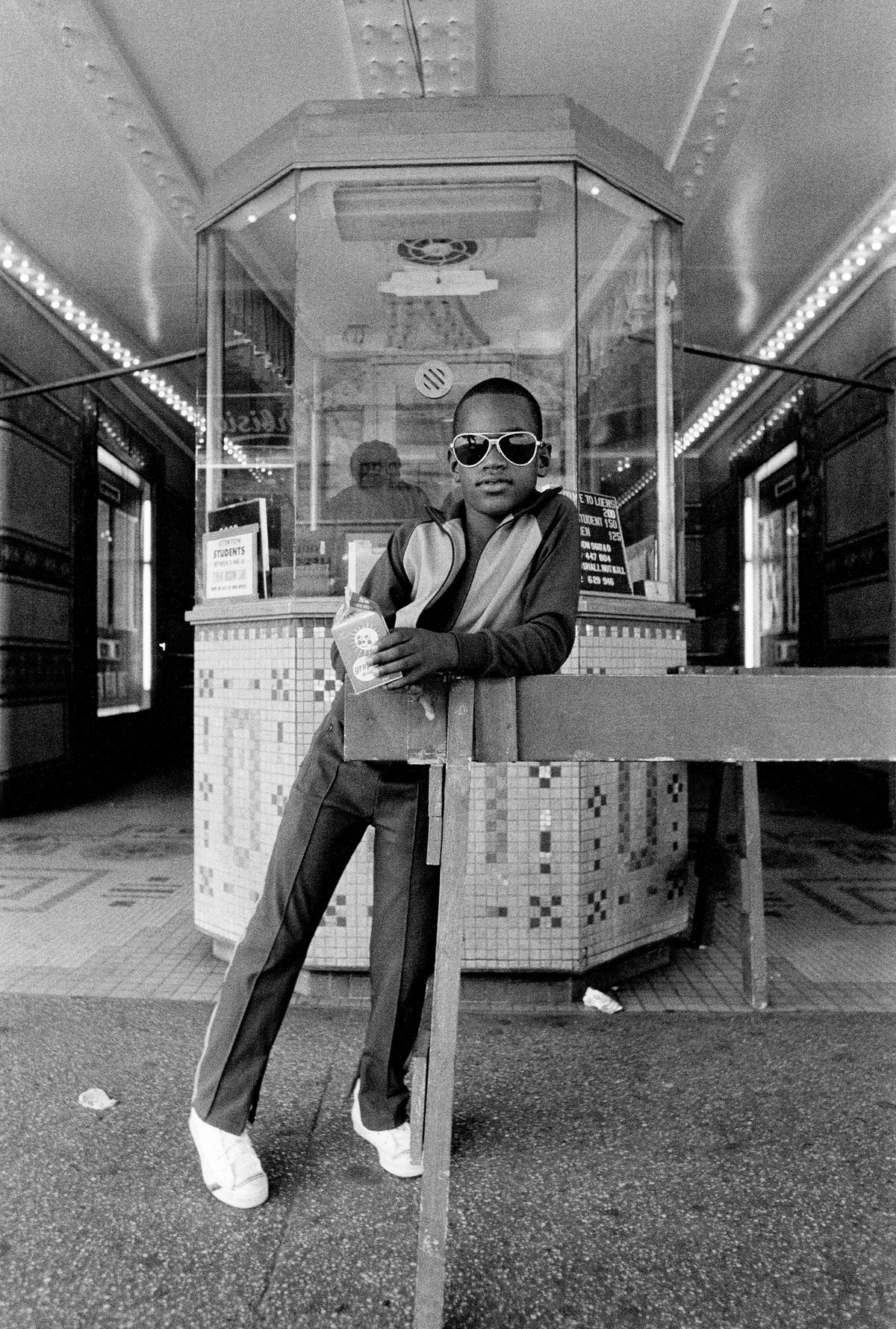 Dawoud Bey, A Boy in Front of the Loew's 125th Street Movie Theater, Harlem, NY from Harlem, U.S.A., 1976.