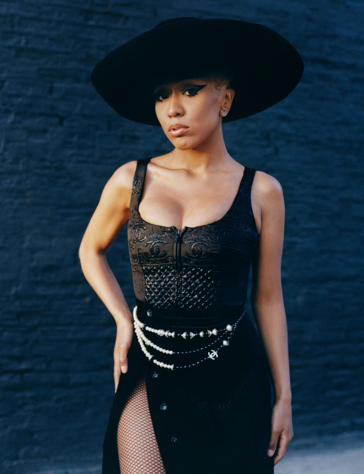 Fousheé wears a Chanel top, skirt, hat, and belt; Capezio fishnets.