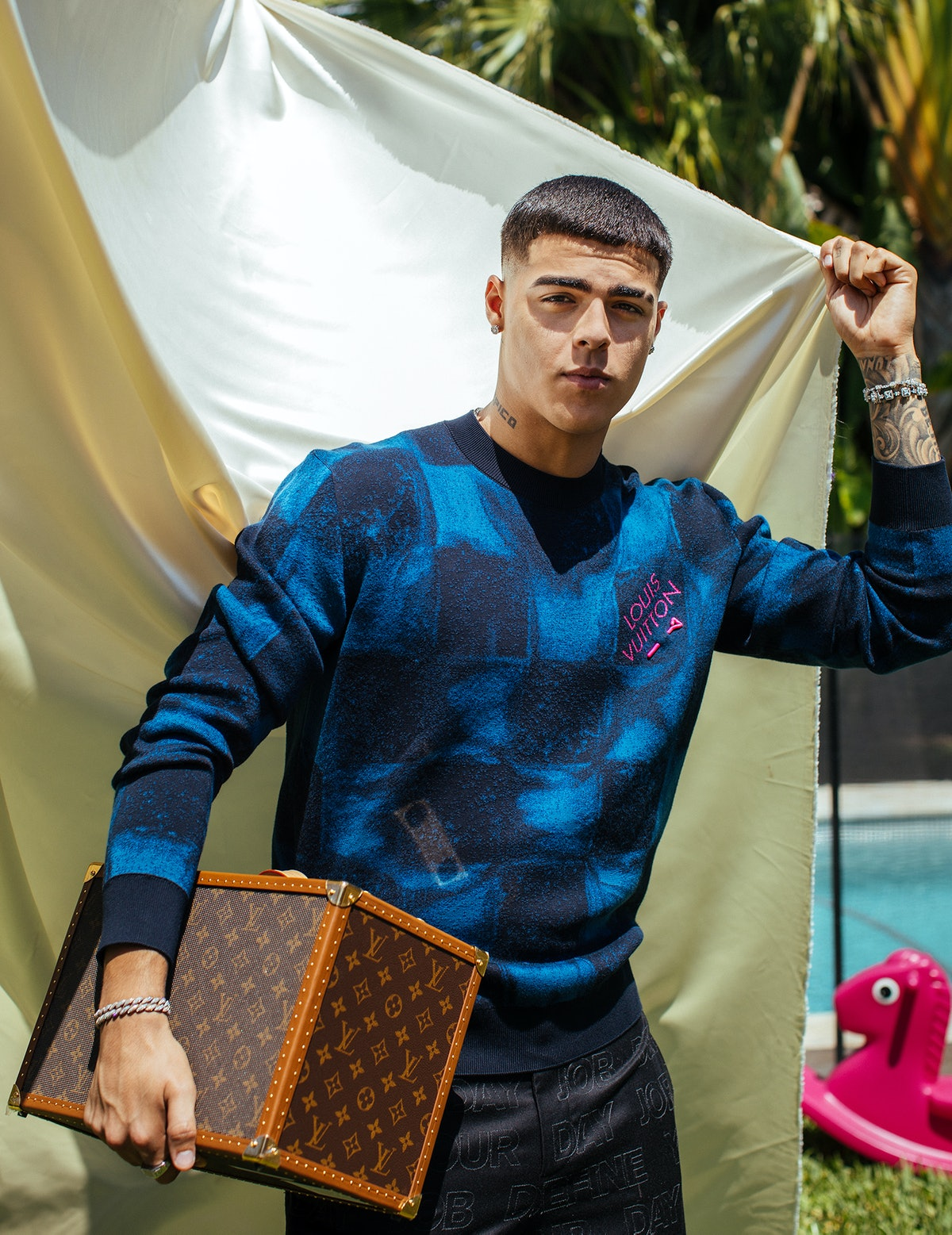 Lunay wears a Louis Vuitton Men's sweater, pants, and speaker trunk; Jewels by Dunn bracelets and rings; his own earrings.