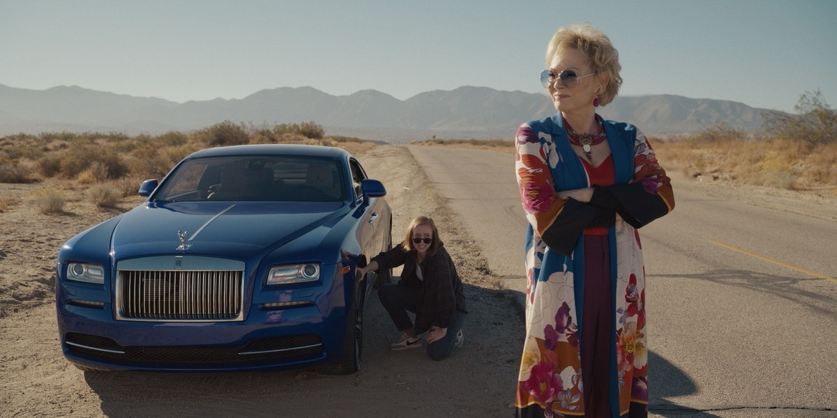 Jean Smart standing, Hannah bending down by a car