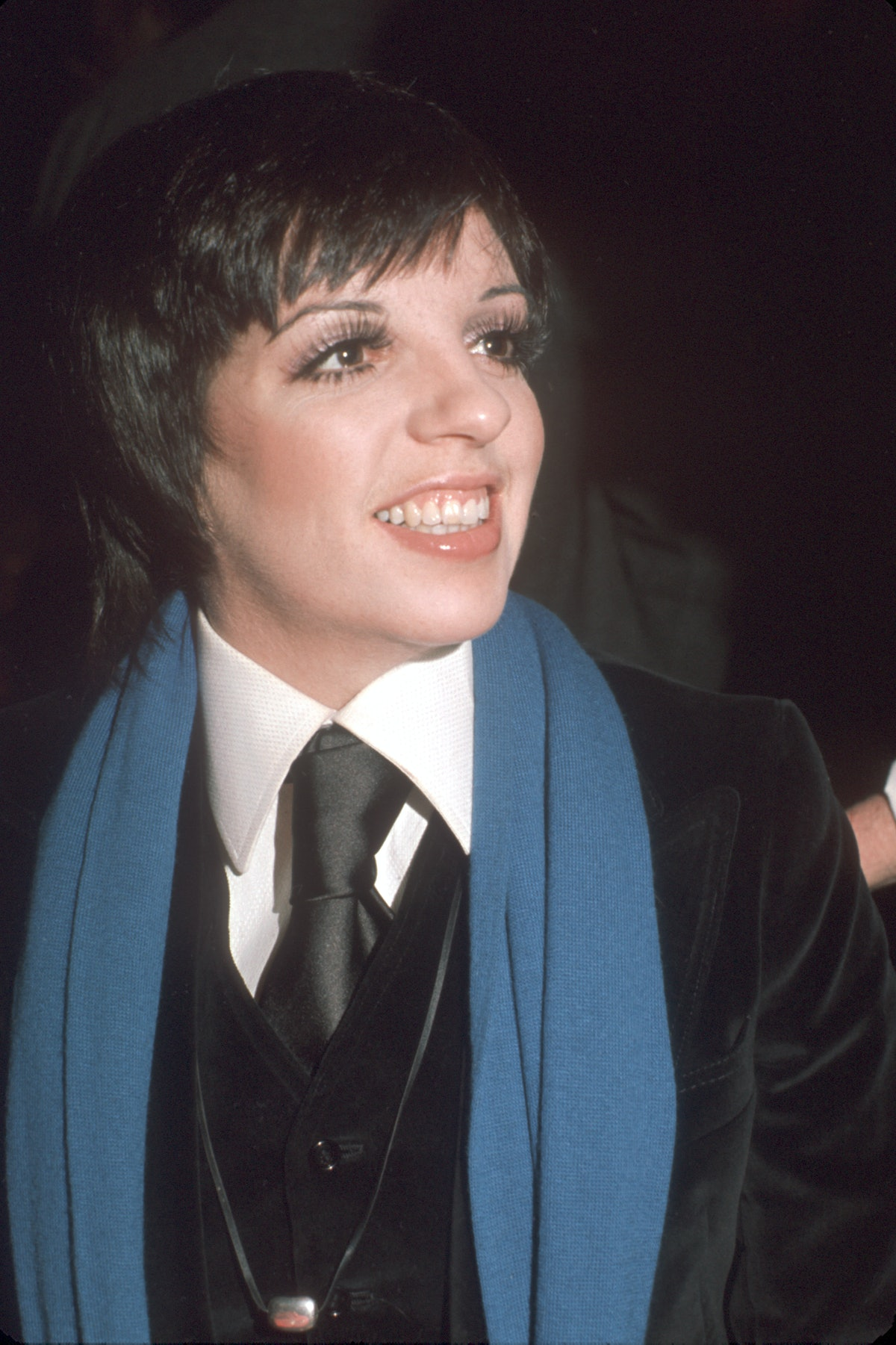 Liza wearing a black suit and tie with blue scarf