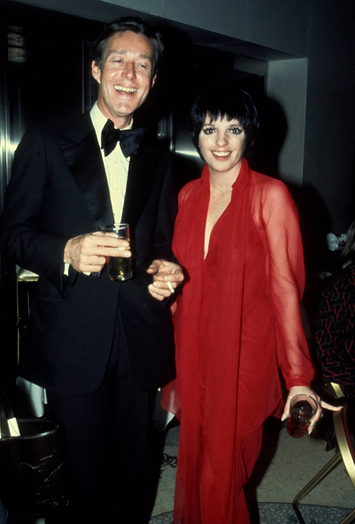 Halston in a black suit, Liza in red gown
