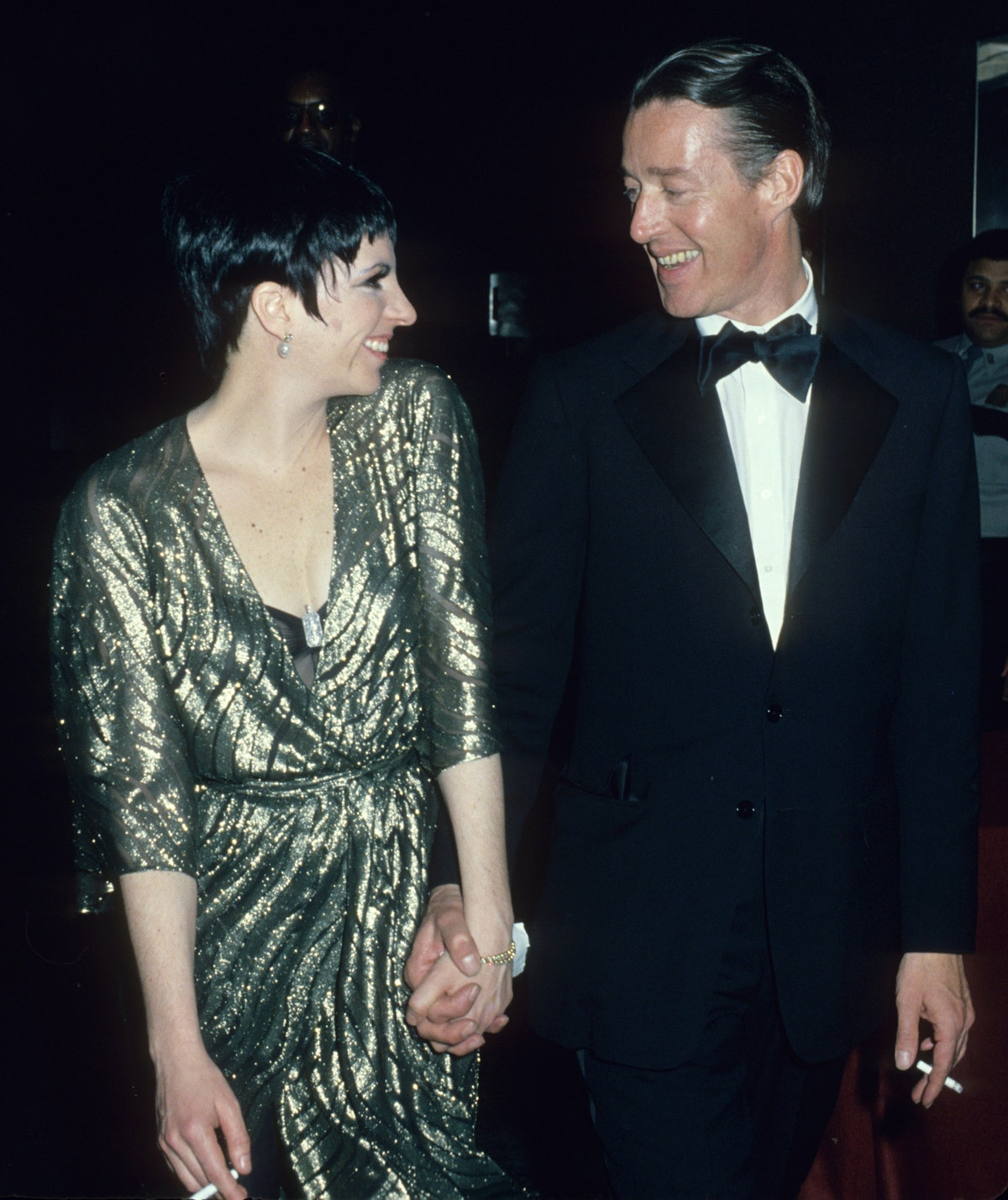 Liza wearing gold Halston in a black suit