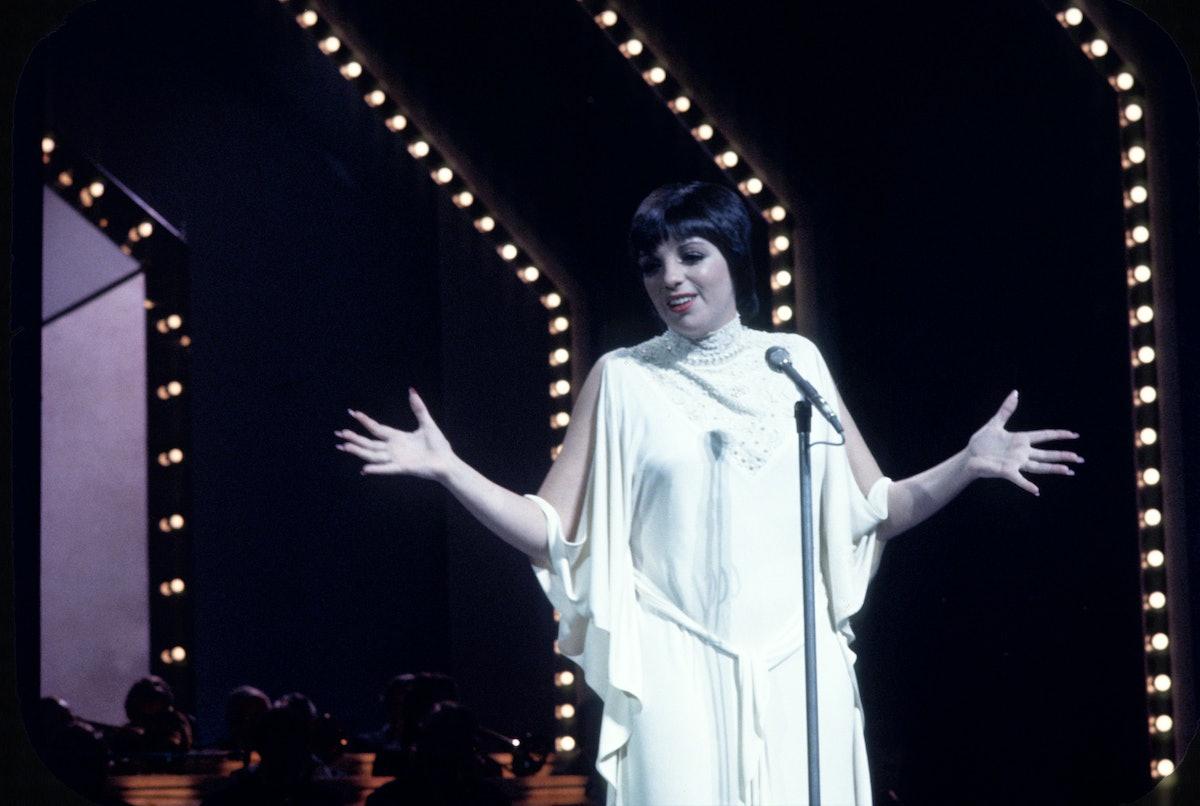 Liza wears all white gown