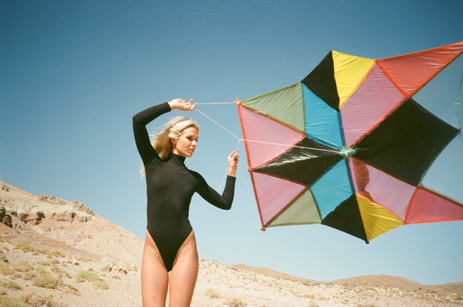 A portrait of Natalie Bergman. She wears a black leotard and is holding a colorful kite. The sky and...