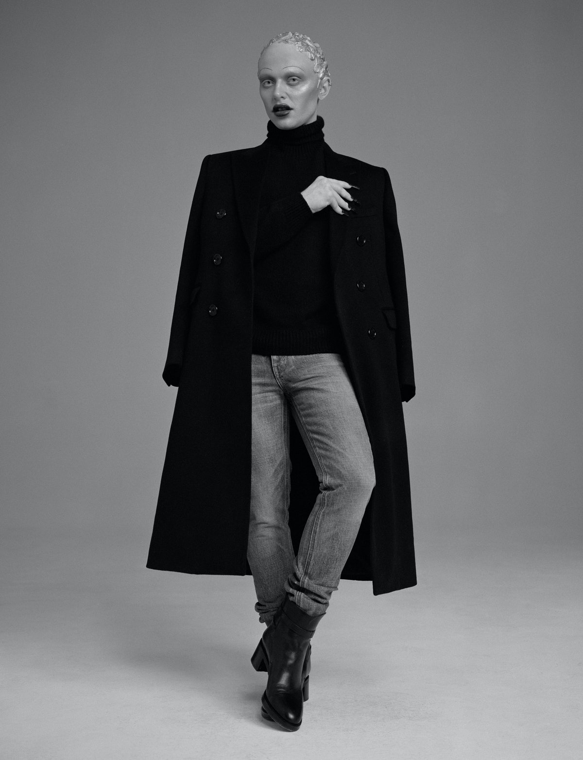 Bimini Bon Boulash wears a Celine by Hedi Slimane coat, sweater, jeans, and boots.
