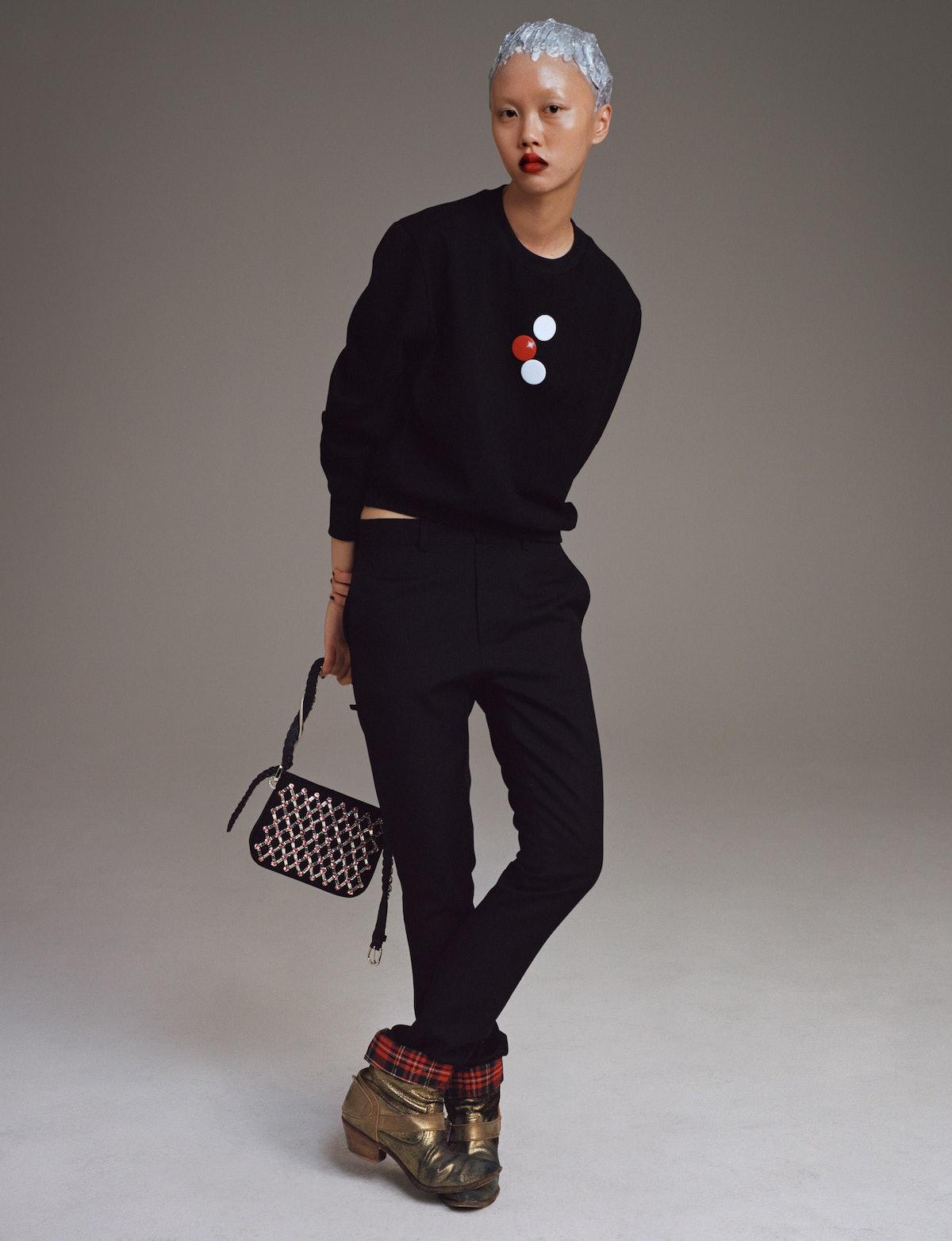Model Jan Baiboon wears a Stefan Cooke sweater and pants; Miu Miu bag; vintage Junya Watanabe boots.