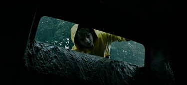 kid looking into gutter in yellow raincoat