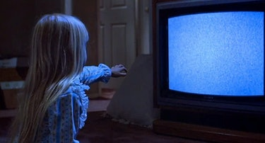 Heather O'Rourke reaching towards tv with static for Poltergeist