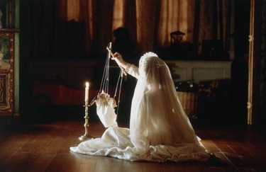 girl with veil holding a puppet near a candle
