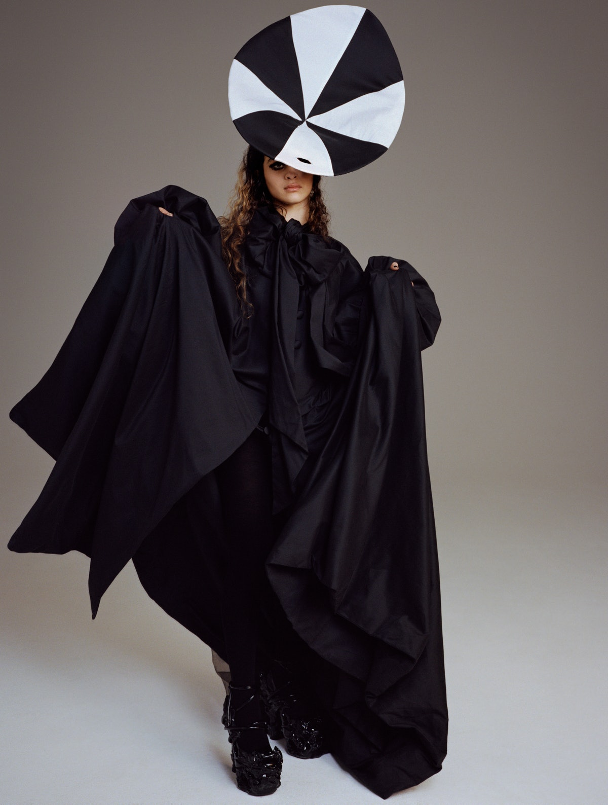 Deba Hekmat wears a Connor Baxter gown and headpiece; Comme des Garçons tights; Del Core shoes.