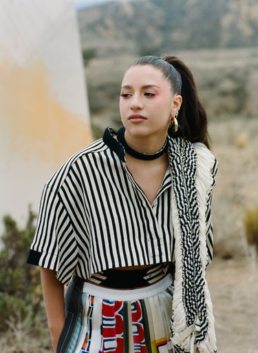 Former 'Dance Moms' star Kenzie Ziegler wears a black and white striped Louis Vuitton shirt while po...