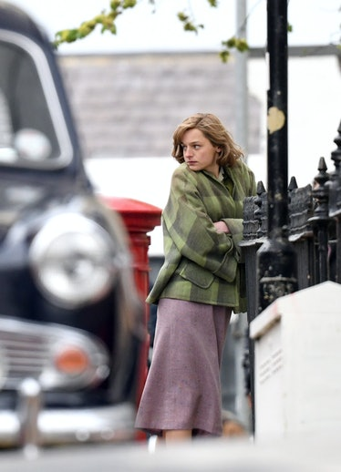 Emma Corrin wearing a green coat
