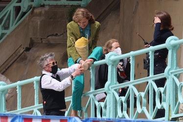 Emma Corrin climbing over a railing