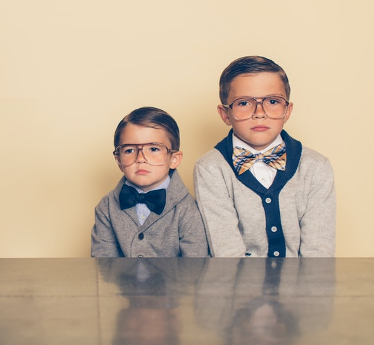 two young brothers wearing retro glasses, cardigans, and bowties