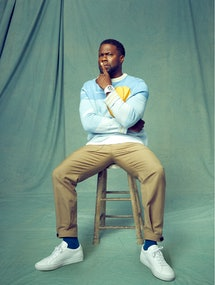 Kevin Hart sits on a stool in front of a green backdrop wearing a blue Victor Li sweater with a yell...