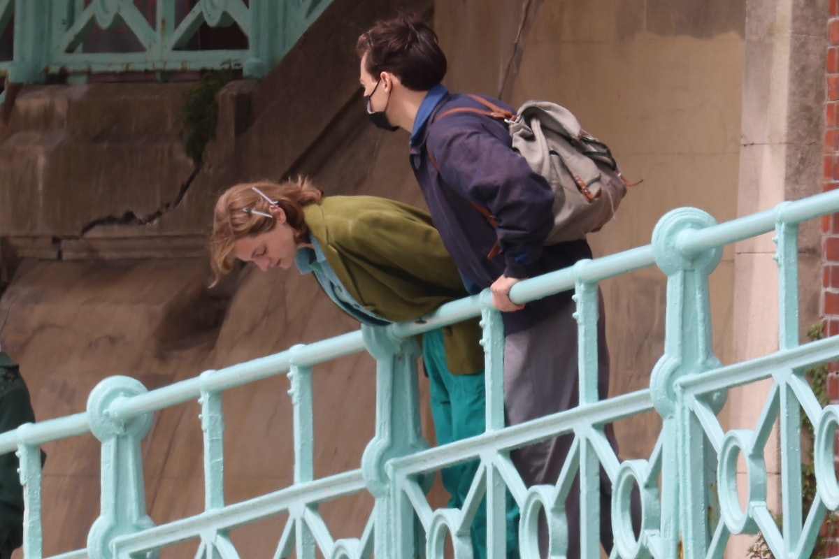 Emma Corrin and Harry Styles leaning over a railing