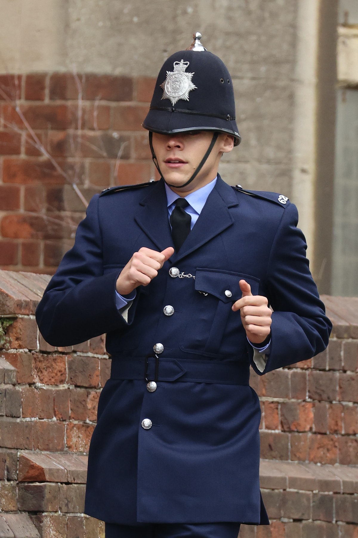 Harry Styles dressed as a cop and running