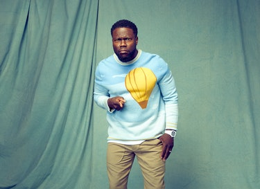 Kevin Hart points at the camera while wearing a blue Victor Li sweater with a yellow hot air balloon...