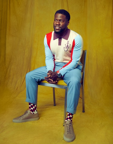 Kevin Hart wears a red, yellow, and blue JW Anderson sweater while sitting down in a chair for Rompe...