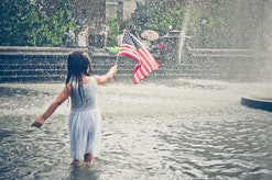 A young girl playing in a park fountain, holding the American Flag