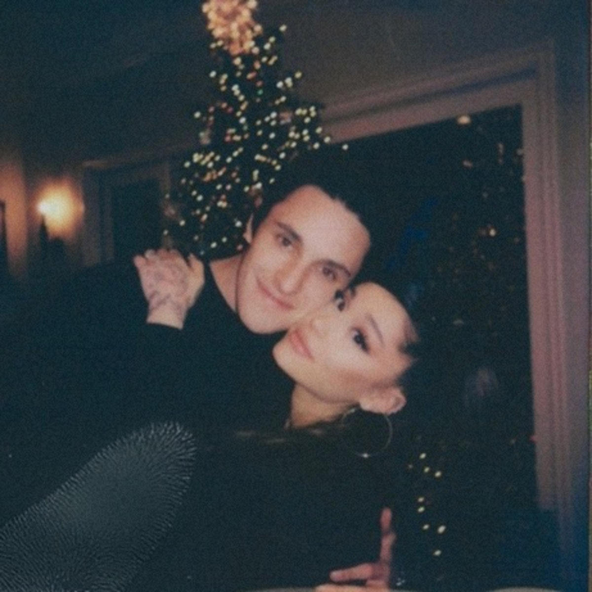 Dalton and Ariana hugging in front of a Christmas tree