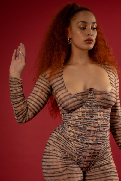 A photo of Jorja Smith. She's wearing a striped cat suit, and stands against a red background. Her eyelids and lips are glossy and she's looking down.