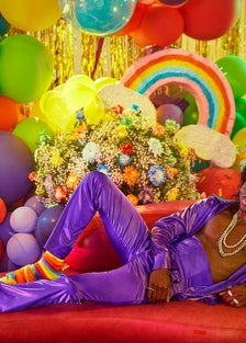 lil nas x reclining in a purple outfit