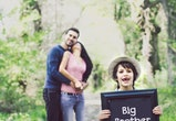 "boy holding ""big brother"" sign with pregnant mom and dad in the background"