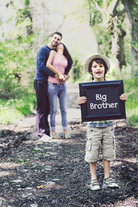 """boy holding """"big brother"""" sign with pregnant mom and dad in the background"""