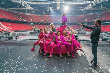 Pink surrounded by performers on a couch with her daughter standing on top