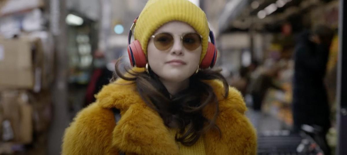 Selena Gomez wearing a yellow beanie and teddy coat