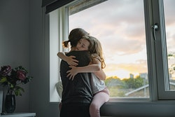 Young girl getting a big cuddle from her mother, in front of a large picture window.