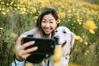 Woman posing for selfie with dog.