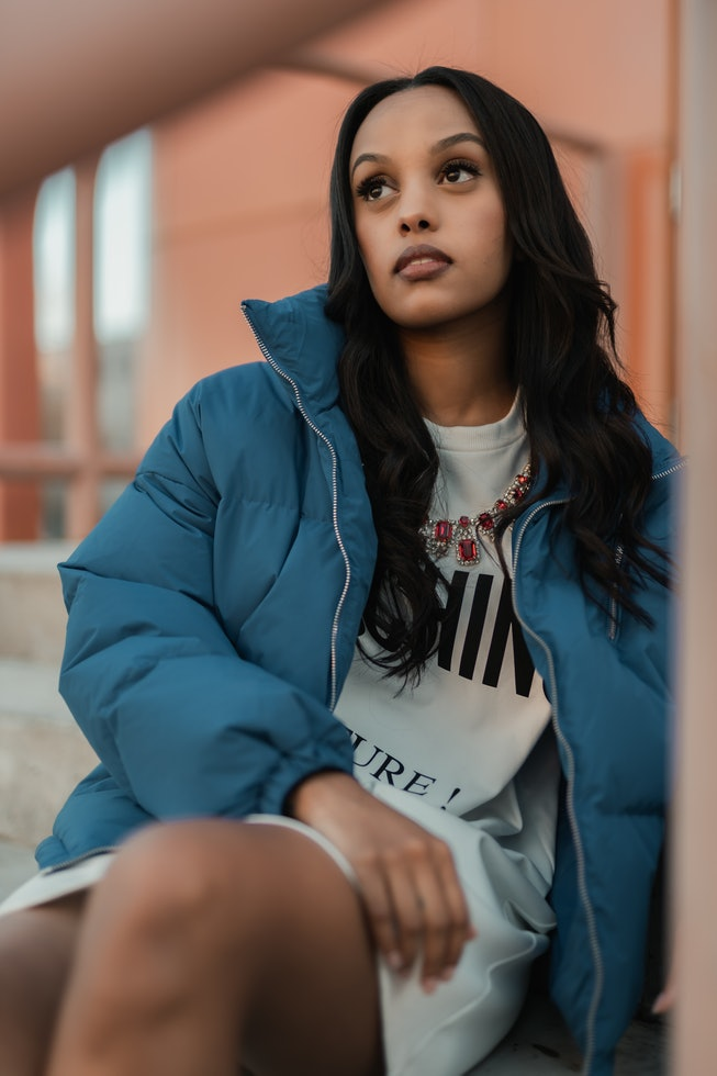 A portrait of Ruth B in a blue buffer jacket and white T-shirt dress.