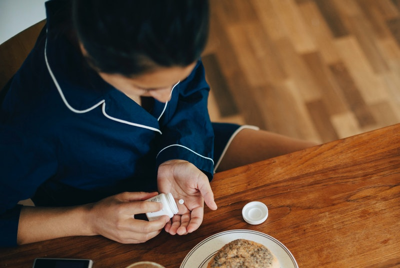A woman taking medication.