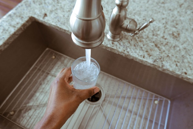 closeup of hand filling up a glass of water at sink