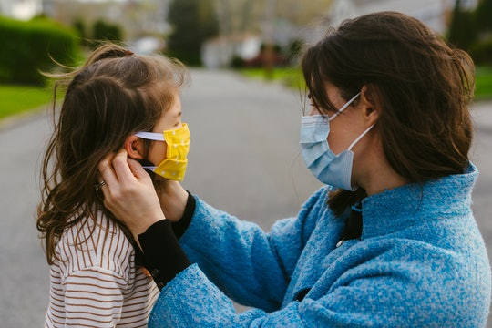 Mother wearing mask adjusts mask on small child